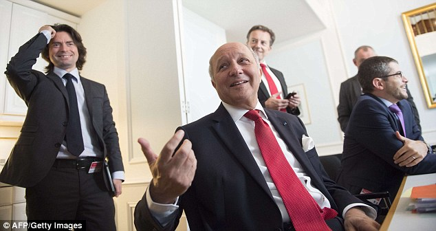 Jovial: French Foreign Minister Laurent Fabius (centre) briefs French journalists at the Palais Coburg Hotel