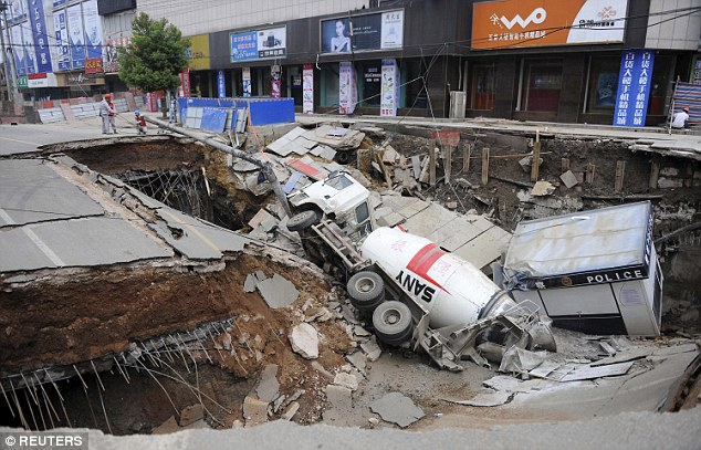 Swallowed up: A cement truck was pulled into the ground when a road collapsed in eastern China on Monday