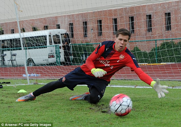 Wojciech Szczesny gets down low to make a save as he is put through his paces in Singapore on Thursday