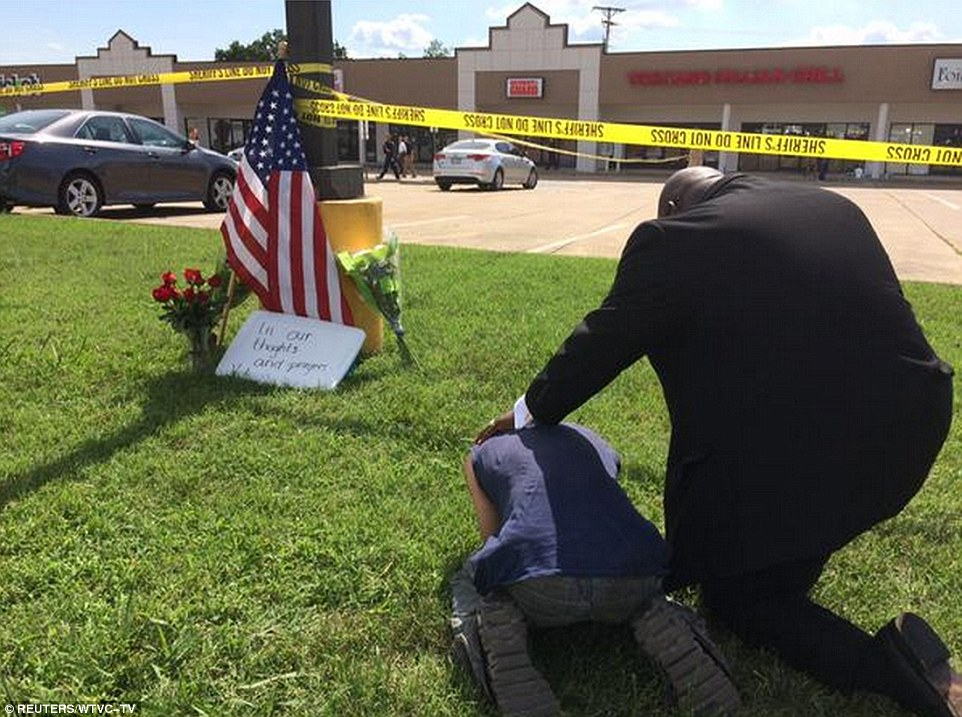 Grief: A pastor prays over a sobbing citizen outside the recruitment center that was targeted during the attack