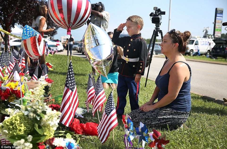 Never forgotten: Blake Miller and his mother Ashley are pictured paying their respects to the four slain marines today. Blake's father is a lieutenant in the marine corps