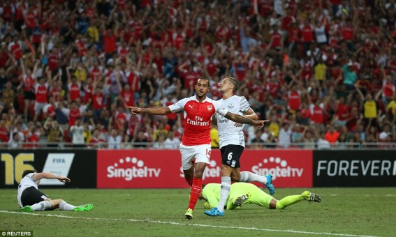 Goalscorer Walcott wheels away in celebration as as the fans in the background celebrate his winner as Arsenal see off Everton