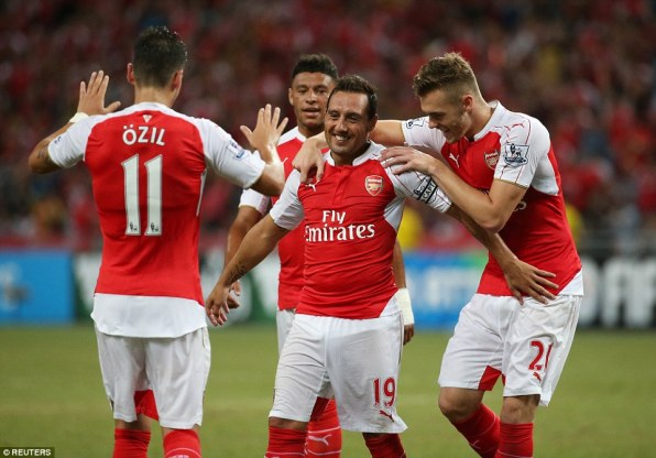 Captain for the day Cazorla is mobbed by his Arsenal team-mates as the Spanish midfielder celebrates scoring in the Asia Trophy final
