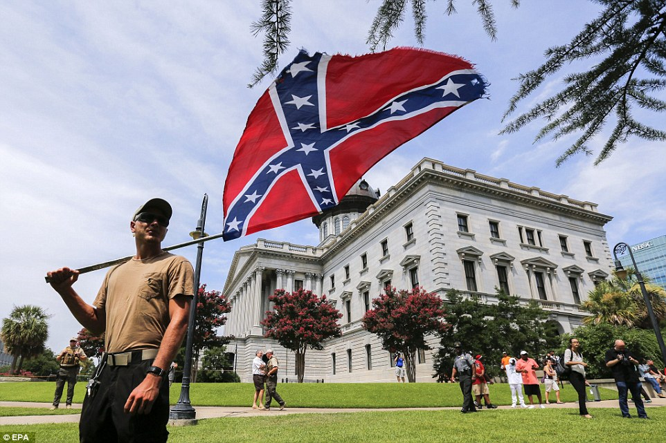 A protester holds the Confederate flag over his shoulder in the midst of the demonstrations