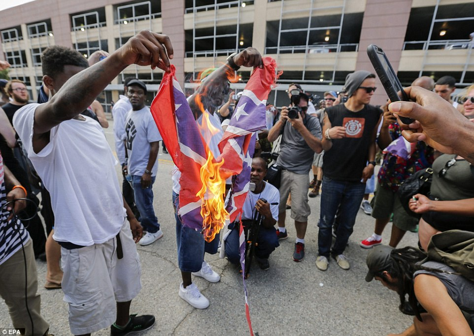 A second man holds up the burning Confederate flag in front of photographers