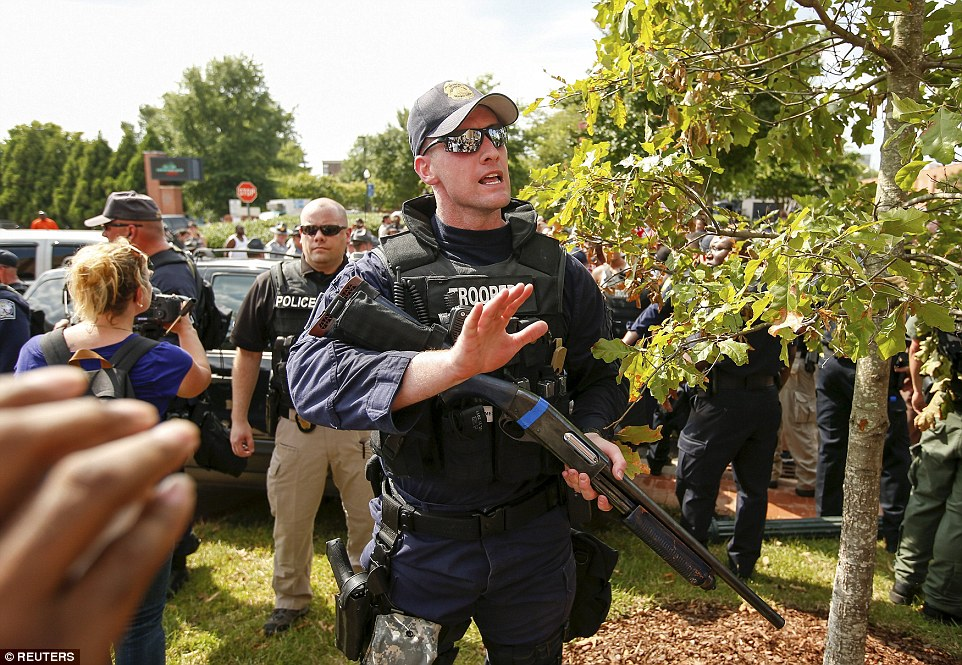 A South Carolina State Trooper yells for protesters to get back after a member of the Ku Klux Klan crashed into a light pole