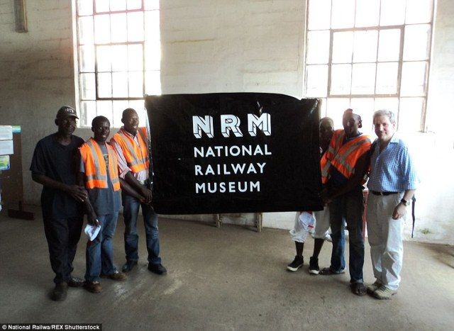 British heritage:Colonel Steve Davies hands over old-branded materials to Sierra Leone museum workers - which came from the UK's National Rail Museum, based in York