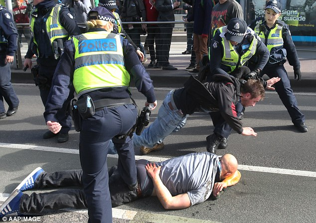 A United Patriots supporter covered in pepper spray lays on the ground as police force fellow protestor to his knees