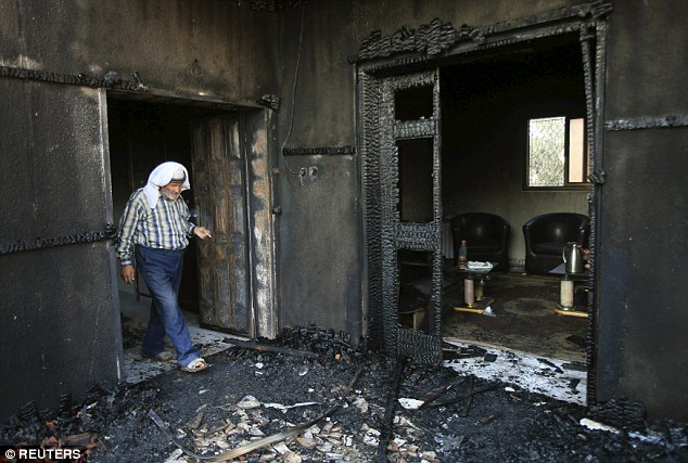 Gutted: Suspected Jewish extremists have set fire to two Palestinian homes in a West Bank village, killing an 18-month-old boy and critically injuring his parents