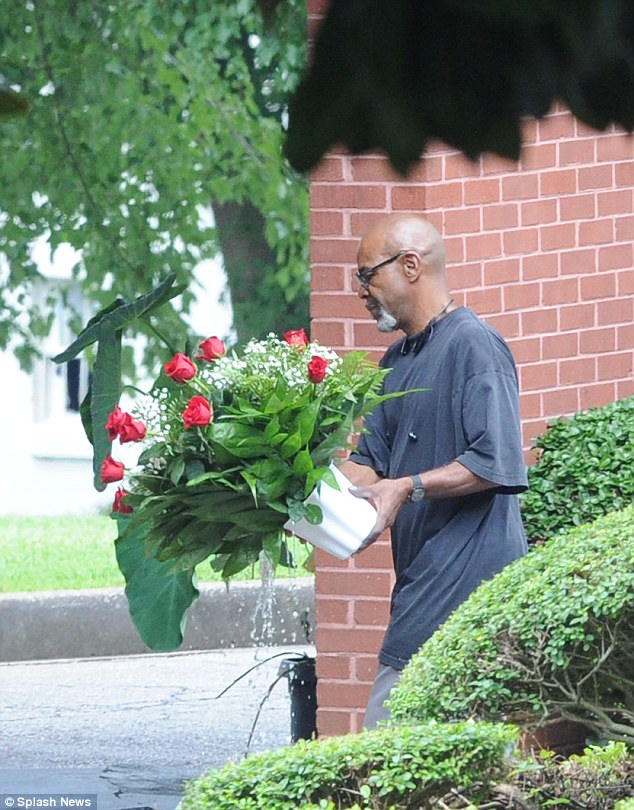 Red roses: Here, a relative is seen arriving with a delicate bouquet for young Bobbi's send-off