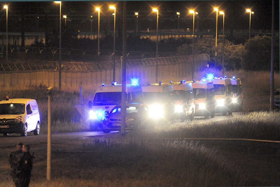 Police response: A fleet of French police vans make their way to the chaotic scene in Calais last night