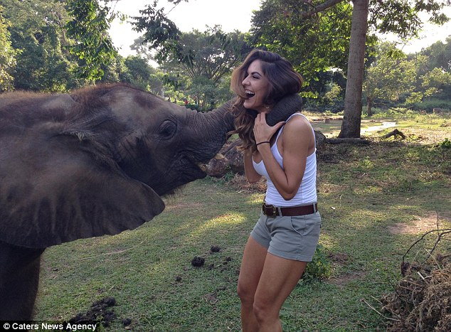 The model, 24, who has featured in Sports Illustrated, plays with a baby elephant during a conservation trip