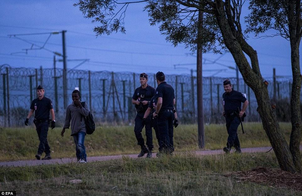 Policías franceses escoltan migrantes junto a una carretera cerca de las vías del tren Eurostar en Calais anoche