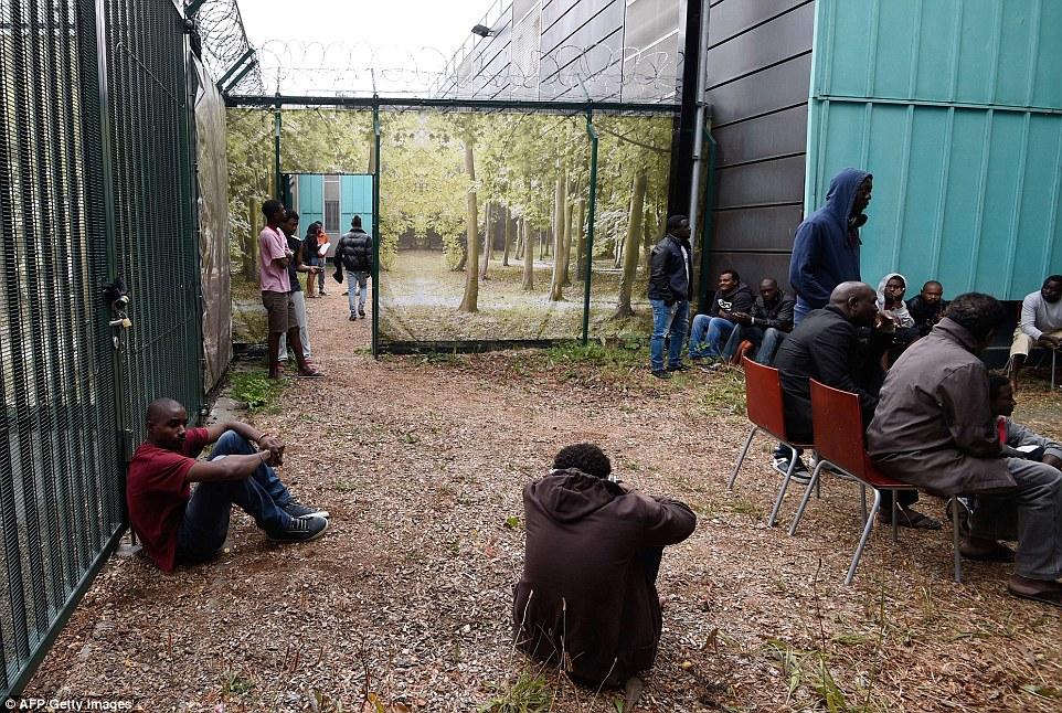 Bloqueado: Un grupo de jóvenes africanos se sientan cerca de la puerta cerrada de un centro de asistencia Emaús de gestión para los migrantes en el este de París, que ha sido ocupadas por sus residentes desde el amanecer