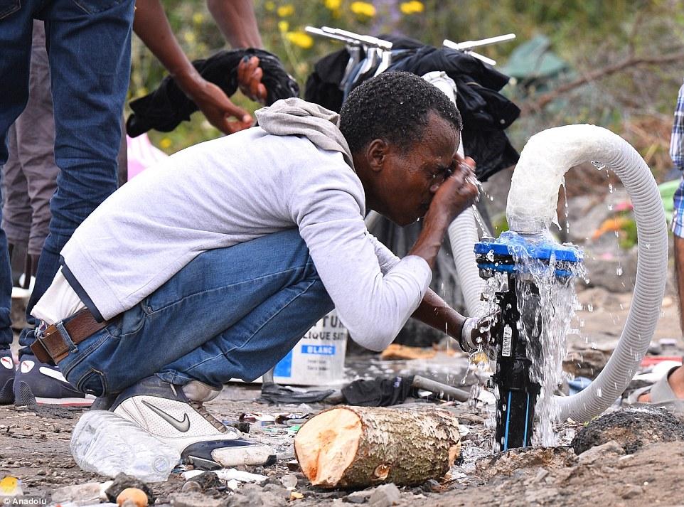 Un migrante se lava la cara en un campamento cerca de Calais el día de hoy.  Él es parte de un grupo tratando de llegar a Gran Bretaña