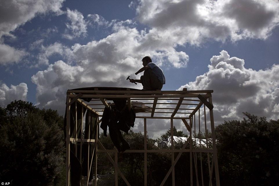 Ismael Nazimi, 40 años, quien perdió su mano izquierda en Afganistán, hace un refugio improvisado en un campamento cerca de Calais