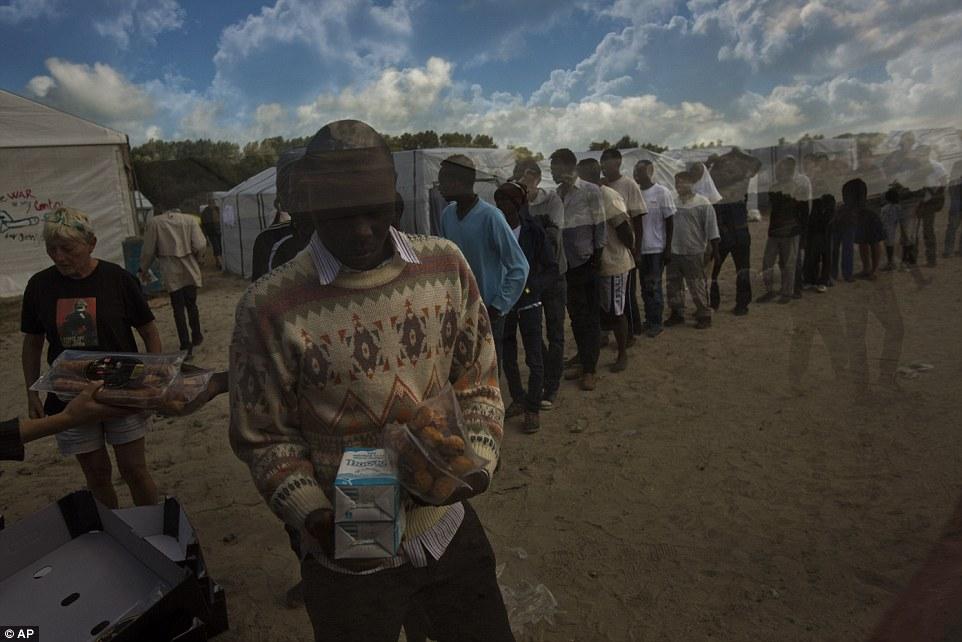 Los migrantes reciben sus raciones de alimentos distribuidas por el Banque Alimentaire de Calais a principios de esta mañana