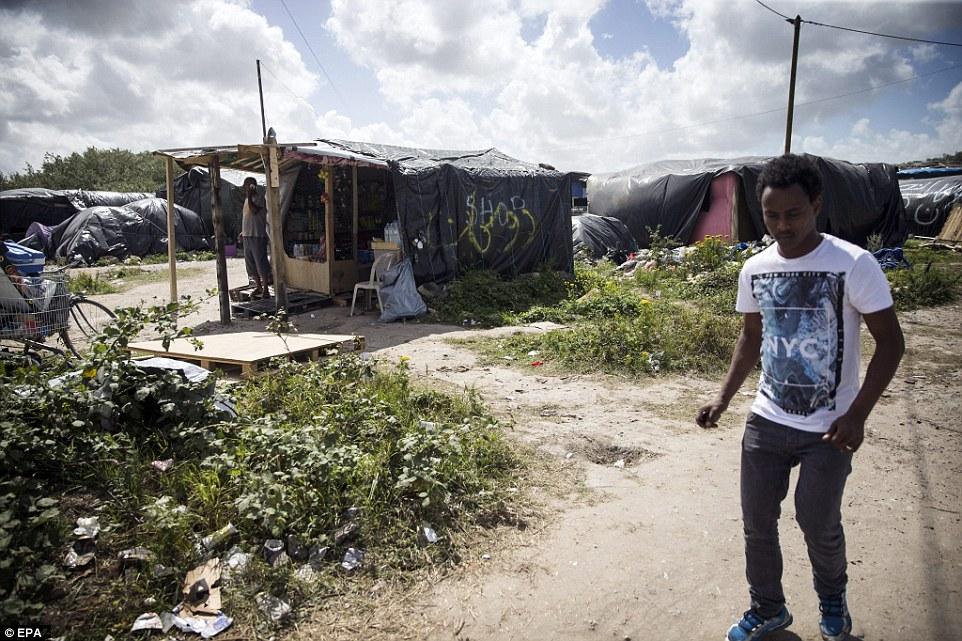 La vida de la selva: Un migrante, quien es el dueño de una pequeña tienda improvisada hecha de madera y hojas en el campamento desmantelado, habla en su teléfono