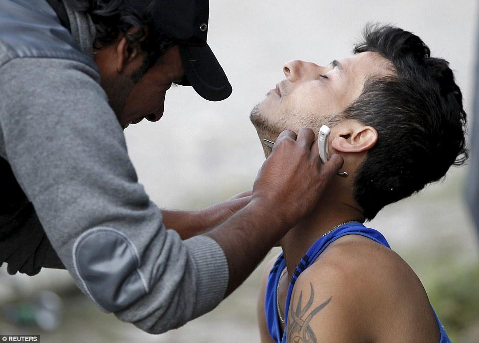 La rutina diaria: Un migrante de Afganistán se afeita por un amigo en el 'Jungle' en Calais como los migrantes continúan con sus vidas diarias