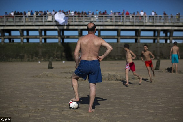 Spectators: People enjoying the sunshine on the beach watched as the march went past