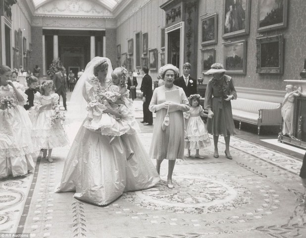 Intimate: Princess Diana is seenholding five-year-old Clementine Hambro, her youngest bridesmaid, as the Queen walks by her side