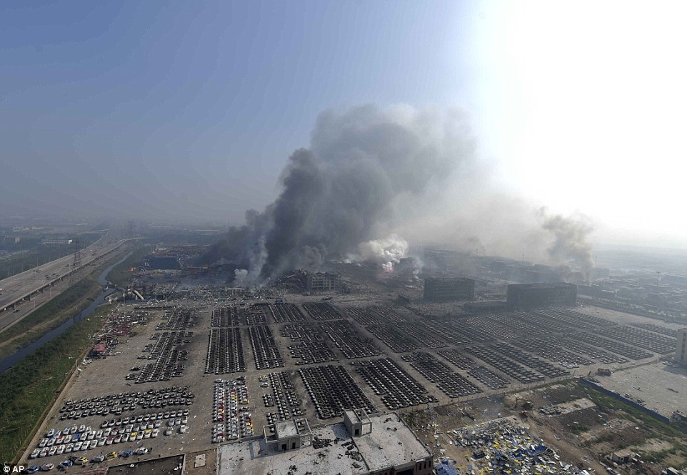 Aftermath: In this photo released by China's Xinhua News Agency, smoke rises from the site of explosions from a nearby building in the Binhai New Area in northeastern China's Tianjin municipality. The explosions claimed the lives of at least 44 people and injured 500 more