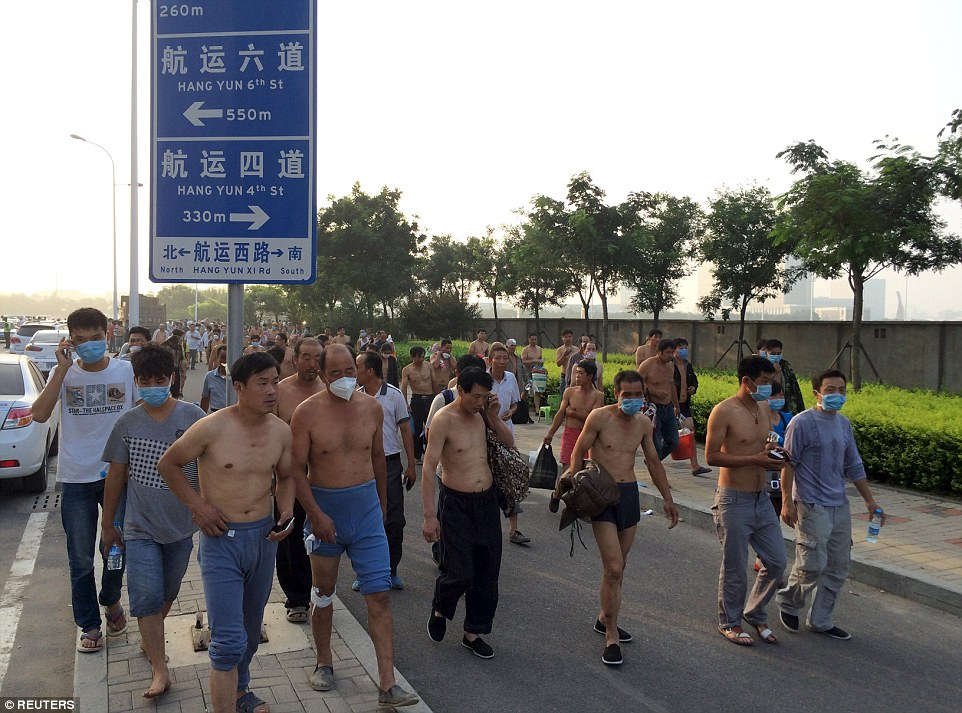 Evacuation: People wearing masks leave their homes for temporary shelters near the site of the explosions at the Binhai new district in Tianjin