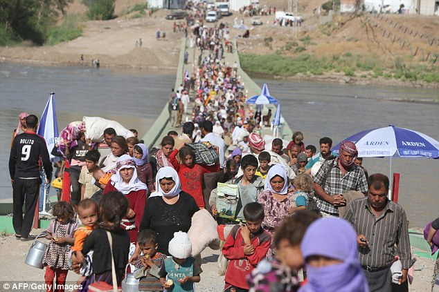 Moving: The beginning of slavery within the group dates back to this time last year, when ISIS fighters invaded villages near Mount Sinjar in Iraq. Displaced Iraqis from the Yazidi community are pictured in August 2014