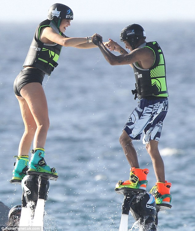 Not shy anymore: Kylie, left, and Tyga, right, held hands as they jetpacked in St. Barts later that afternoon