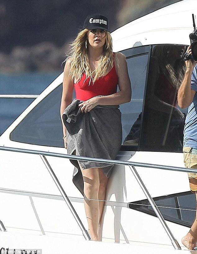Menutupi: Khloe Kardashian memilih untuk Baywatch terinspirasi merah one-piece tetapi ditutupi dengan handuk pantai