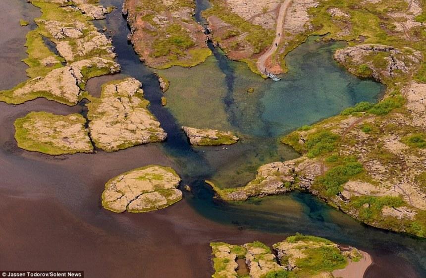 Le spaccature nella terra, che ha molti difetti, valli, vulcani e sorgenti termali, sono causate dalle piastre eurasiatiche e nordamericane in Islanda tirando a parte