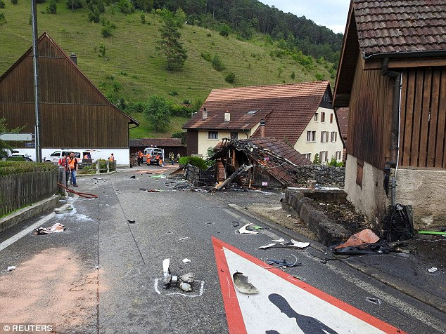 Debris: Plane parts are scattered across the road in front of the barn the pilot crashed into during the show
