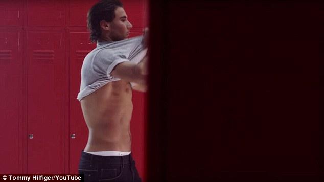 Odizolovanie: Rafael odštartoval video tým, že rýchlo odstránil košeľu, keď vošiel do šatne zdobenej podpisom Tommyho Hilfigera červenej, bielej a modrej farby.