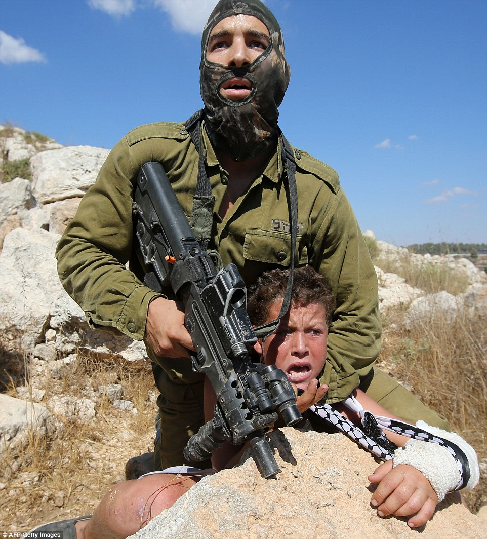 Terrified: An Israeli soldier puts a young boy in a headlock at gunpoint during clashes between security forces and Palestinian protesters following a march against Palestinian land confiscation to expand the Jewish Hallamish settlement in the West Bank village of Nabi Saleh