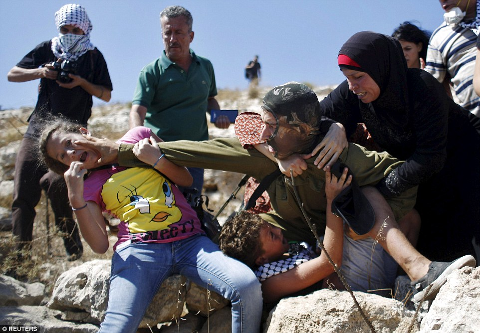 The soldier fights back as the girl tries to prevent him from detaining the boy during a protest in the West Bank village of Nabi Saleh