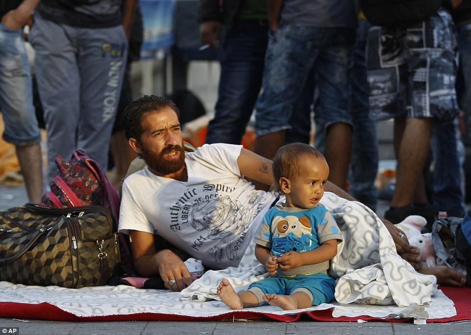 Cerrado: Un migrante y su niño se despierta después de dormir áspero en las calles de Budapest, Hungría, cuando la policía detuvo a subir a un tren a Alemania