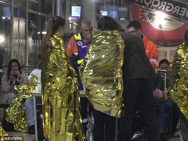 Exhausto: Los pasajeros envueltos en mantas de papel de aluminio térmicas dadas por los servicios de emergencia después de que su tren Eurostar quedó varado en la estación de Calais, después de intrusos fueron vistos cerca del Eurotúnel