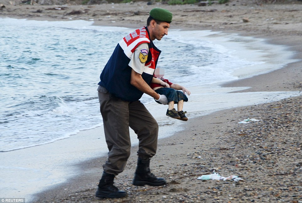 The human cost: A policeman on a Turkish beach gently recovers the bodies of two brothers drowned as their family tried to make their way to the Greek island of Kos yesterday