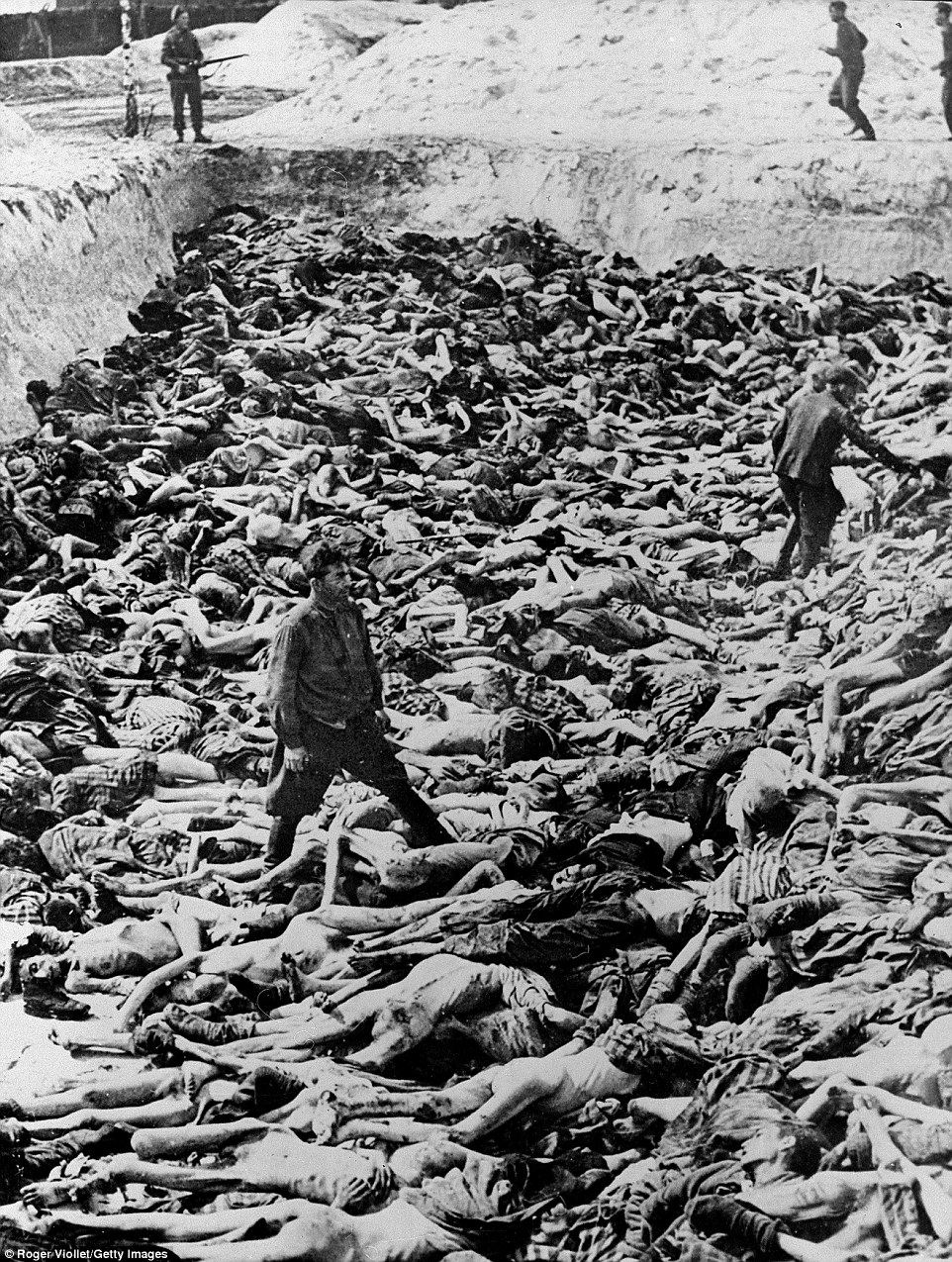 April 1945: Fritz Klein, a Nazi camp doctor who conducted medical experiments on prisoners during the Holocaust, stands among corpses in a mass grave after the liberation of Bergen-Belsen, Germany. Of the 38,500 inmates found barely alive after liberation, about 28,000 subsequently died. Watched by British soldiers, Klein is pictured here being forced to bury the dead. That December, he was sentenced to death and hanged for his role in the atrocities. Bergen-Belsen was the first Nazi camp to be liberated - and gave the world some of the first visual evidence of the horrors of the Holocaust
