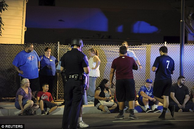 Shocked and confused, the hostages from the restaurant sit on the curb after the diner was stormed by SWAT