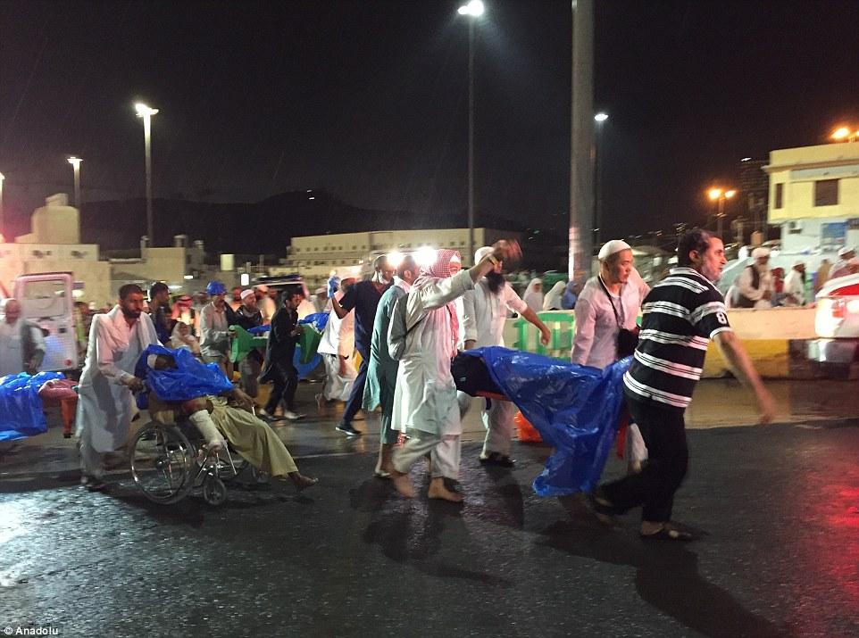 Las escenas de devastación: Las víctimas de la caída de la grúa se realizan en camillas o empujados en sillas de ruedas como la lluvia continúa anclar