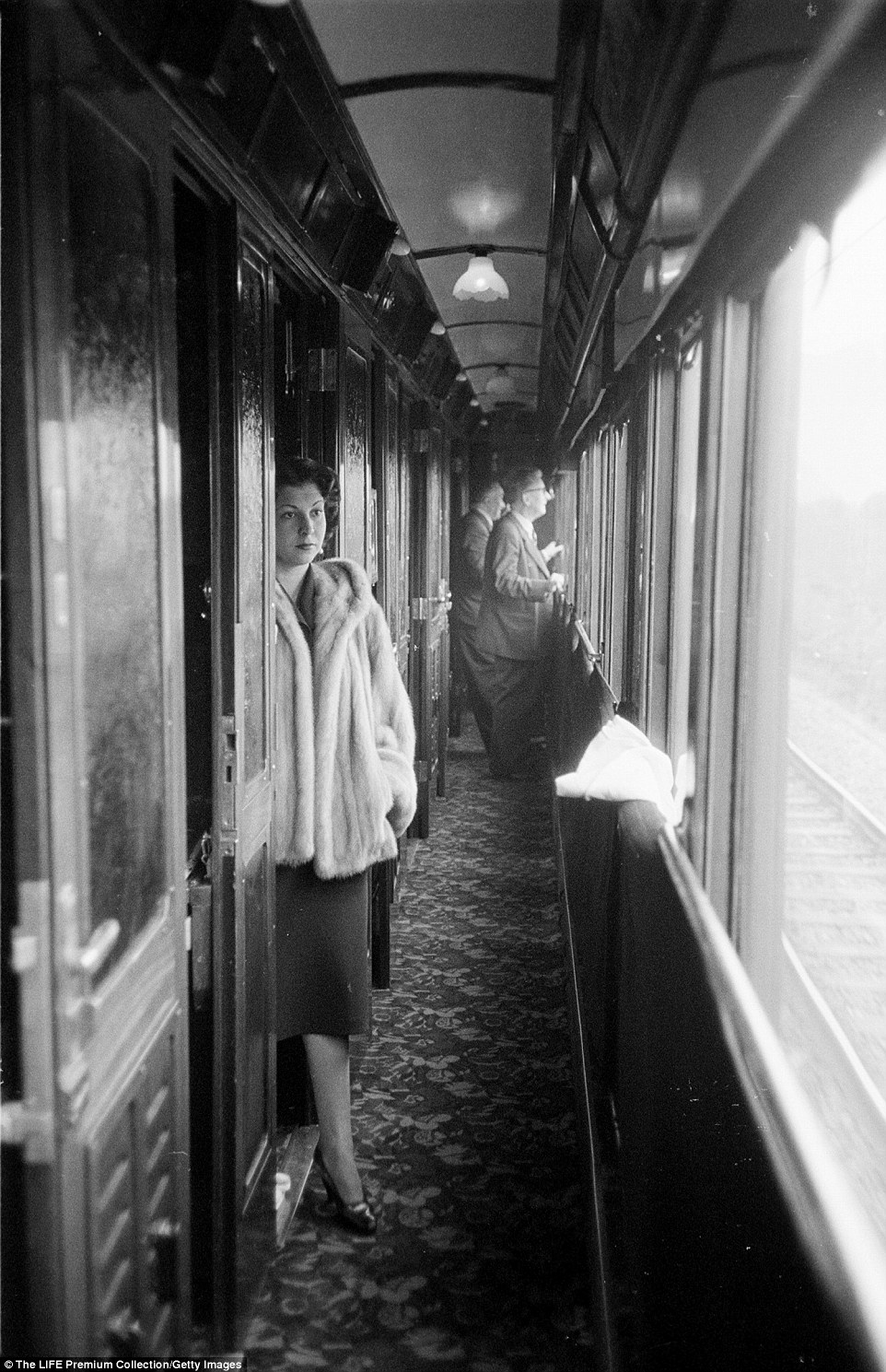 A woman passenger in a fur coat aboard the Simplon-Orient Express gazes wistfully out at the train tracks in this shot from 1950