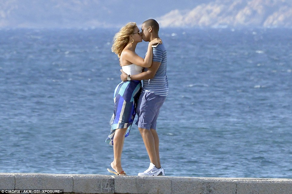 Loved up: Beyonce and Jay Z looked madly in love while sharing a romantic kiss by the seaside on Saturday as they continue their idyllic family break to Sardinia, alongside Blue, their adorable three-year-old daughter and Beyonce's former bandmate Kelly Rowland