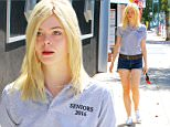September 18, 2015: Elle Fanning spotted with a 'Seniors 2016' shirt and denim shorts on her way to a studio today in Los Angeles, CA.\nMandatory Credit: Lek/INFphoto.com Ref: infusla-294