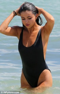 Looking lovely: The beauty smiled as she enjoyed some time to herself in the surf
