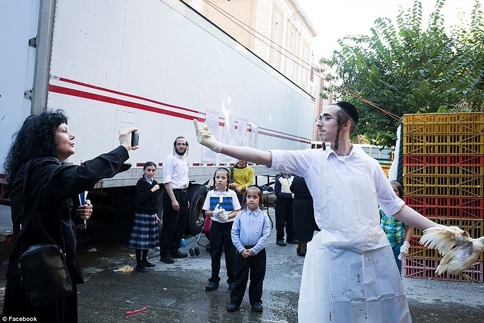 Animal rights campaigners have clashed with members of the Orthodox Jewish community on the streets of New York City over the killing of tens of thousands of chickens during a Jewish ritual (pictured, a Jewish man gives the finger to a protester as she film him)