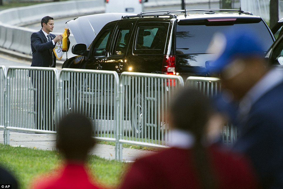 A Secret Service Agent places the Papal flag on a vehicle in preparation of Pope Francis departure from the Apostolic Nunciature, the Vatican's diplomatic mission in Washington, Wednesday, Sept. 23, 2015