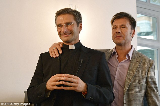 Fired: Father Krzystof Charamsa (pictured left with his partner), who held a post in the Vatican's branch for protecting Catholic dogma, was dismissed after coming out as gay this weekend