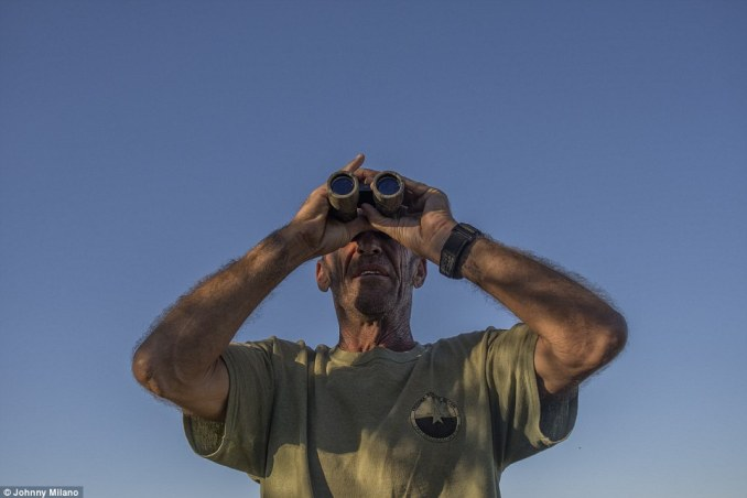 Always on guard: Group chief leader Tim 'Nailer' Foley surveys the hills, using binoculars as he keeps an eye out for activity