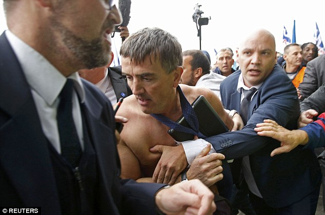 Under attack: A shirtless Xavier Broseta, Executive Vice President for Human Resources at Air France, is evacuated by security after employees interrupted a meeting with representatives staff at the Air France headquarters building at the Charles de Gaulle International Airport in Roissy, near Paris